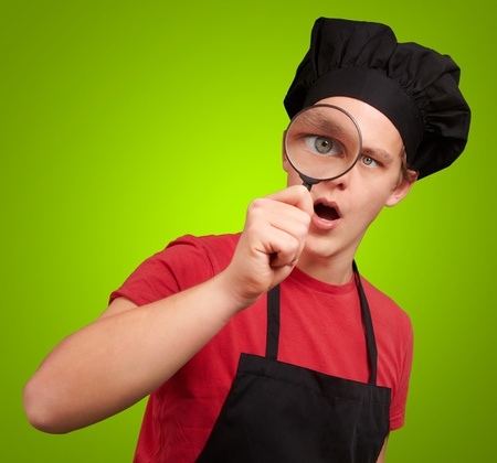 portrait of young cook man looking through a magnifying glass over green photo