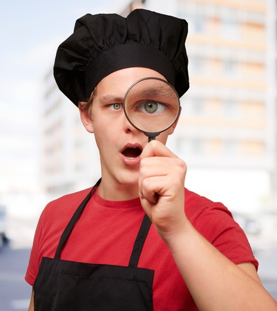 investigate: portrait of young cook man looking through a magnifying glass against a building