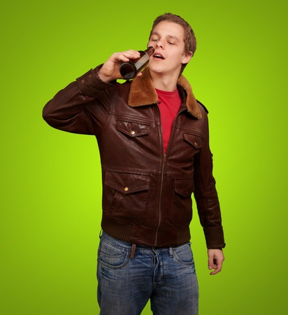 portrait of young man drinking beer against a green background photo