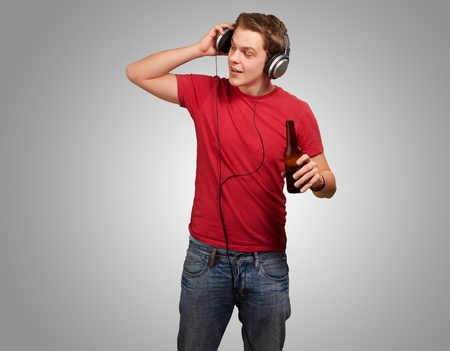 portrait of young man listening music and holding beer on grey background photo
