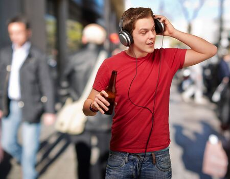 portrait of young man listening music and holding beer at street photo