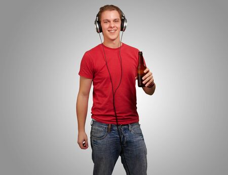 portrait of young man listening music and holding beer over grey background photo