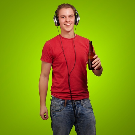 portrait of young man listening music and holding beer over green background Stock Photo - 13280414