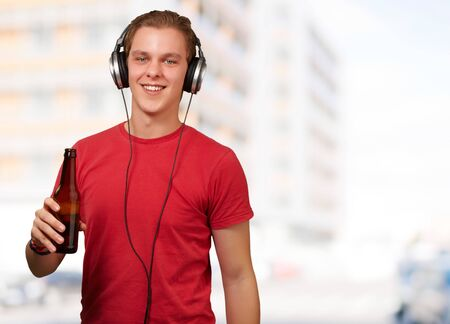 portrait of young man listening music and holding beer against a building Stock Photo - 13280088