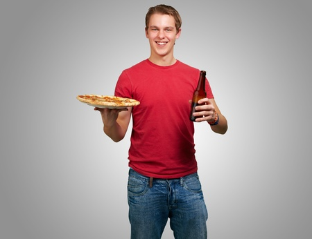 portrait of young man holding pizza and beer over grey background photo