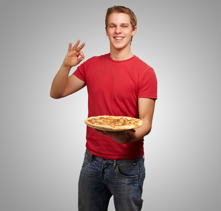 portrait of young man holding pizza and doing good gesture over grey background Stock Photo - 13280493