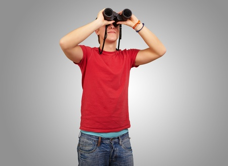 portrait of young man with binoculars over grey background Stock Photo - 13280482
