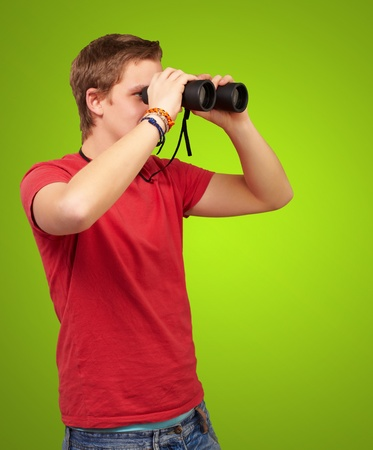 portrait of young man looking through a binoculars over green background photo