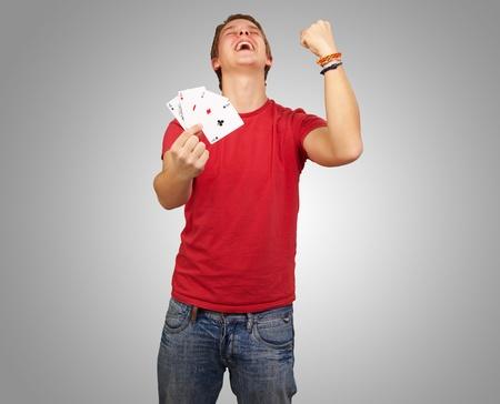 Retrato de hombre joven haciendo un gesto de ganador a jugar al poker sobre gris photo