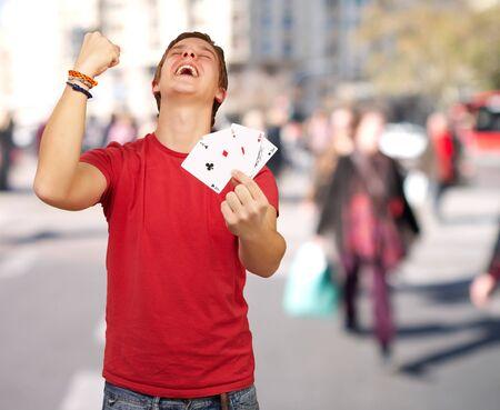 Retrato de hombre joven haciendo un gesto de ganador a jugar al poker en el lugar lleno de gente photo