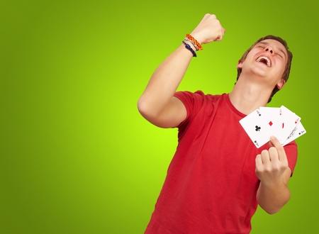 cartas de poker: Retrato de hombre joven haciendo un gesto de ganador a jugar al poker sobre el verde