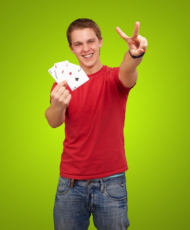 portrait of young man doing a victory gesture playing poker over green background photo
