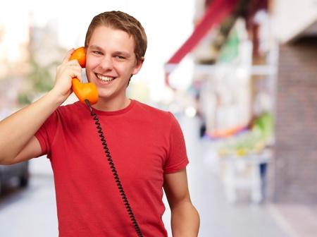 portrait of young man talking with vintage telephone at street photo