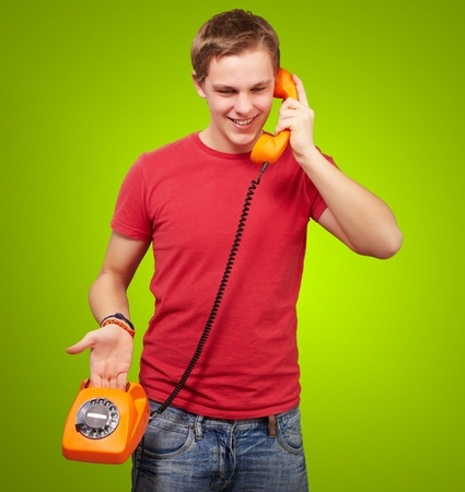 portrait of young man talking on vintage telephone over green background photo