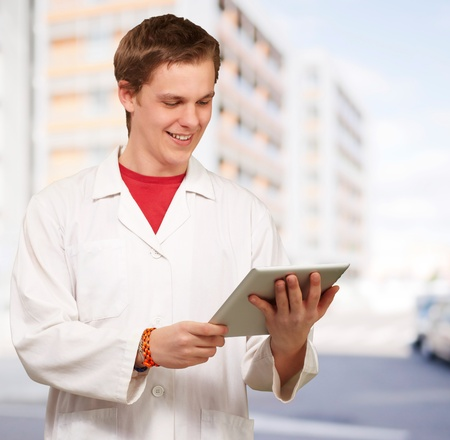 portrait of young academic holding a digital tablet against a building photo