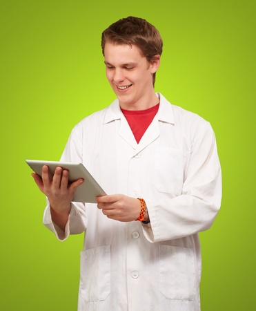 portrait of young academic holding a digital tablet over green background photo