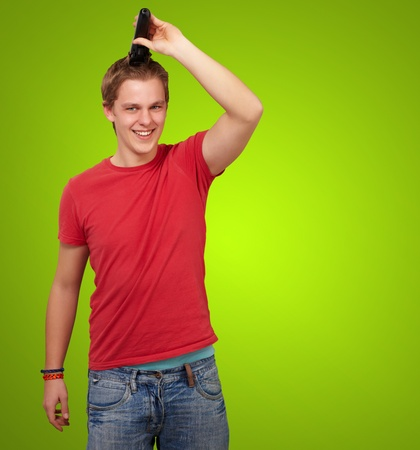 portrait of young man cutting his hair over green background photo