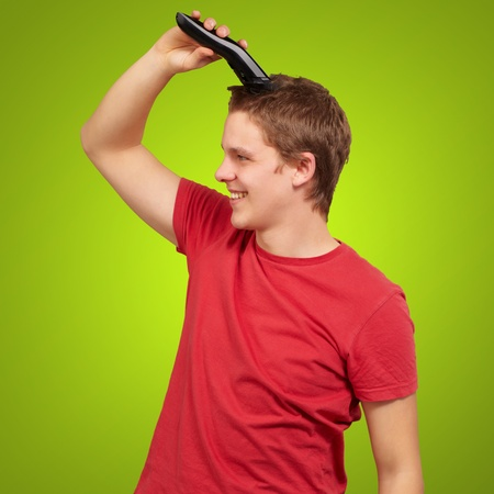 electric razor: portrait of young man cutting his hair over green background Stock Photo
