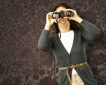 portrait of midlle aged woman looking with binoculars against a vintage wall photo