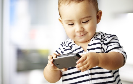 young boy playing with a telephone, indoor photo