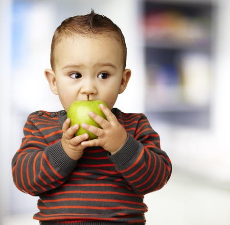 young boy eating a green apple against a kitchen background photo