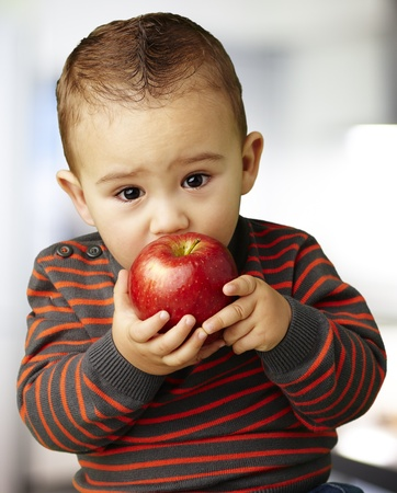 kid eating a red apple against an abstract background photo
