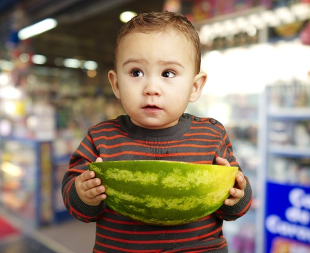 young boy holding a watermelon against a candy shop photo