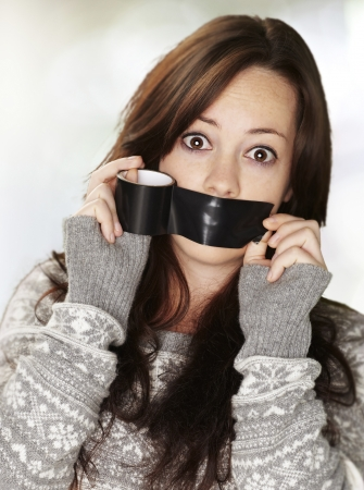 young woman silencing herself with a black tape against an abstract background Stock Photo