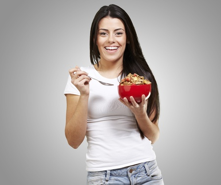 woman holding a delicious red breaksfast bowl against a grey background background photo