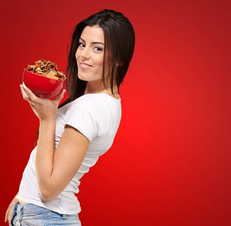 red jeans: Beautiful Healthy Woman Holding Bowl Of Cornflakes On Coloured Background