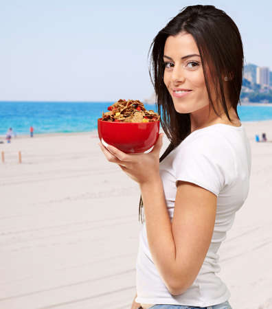 Beautiful Healthy Woman Holding Bowl Of Cornflakes On Coloured Background At Beach Stock Photo - 13280464