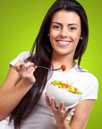 portrait of healthy woman eating salad against a green background Stock Photo - 13280533
