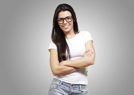 mani incrociate: bella giovane donna con gli occhiali che attraversano le sue armi contro uno sfondo grigio