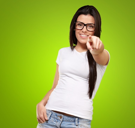 picking fingers: portrait of young woman pointing with finger against a green background Stock Photo