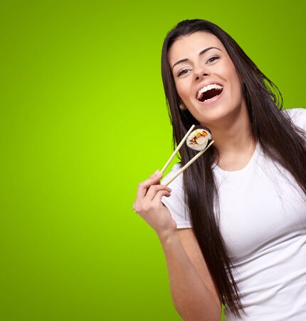 portrait of young woman holding sushi against a green background photo