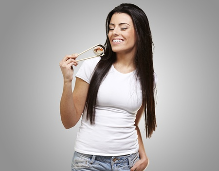 young woman eating a sushi piece against a grey background photo