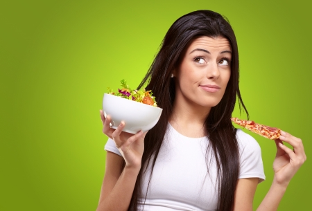 portret van de jonge vrouw te kiezen pizza of salade tegen een groene achtergrond Stockfoto
