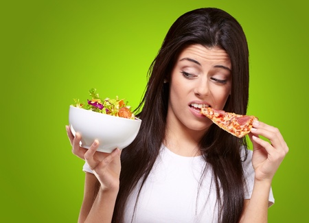 over eating: portrait of young woman eating pizza and looking salad over green