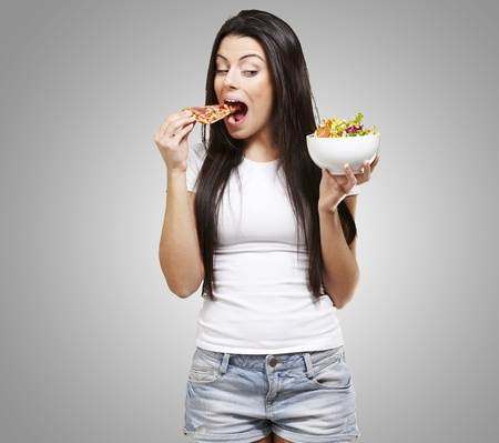 woman choosing a slice of pizza instead of a salad against a grey background Stock Photo - 13280458
