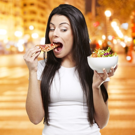 woman choosing a slice of pizza instead of a salad against a city night background photo