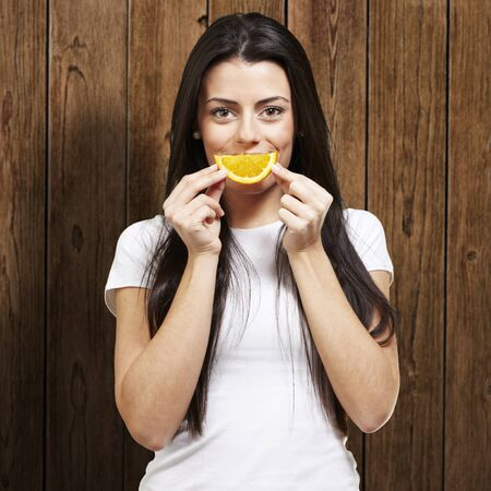 woman with an orange slice as a smile against a wooden background Stock Photo - 13280407