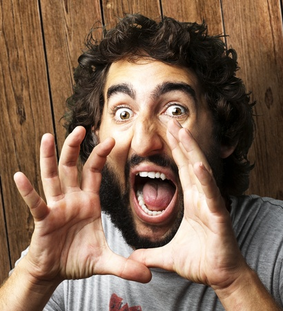 portrait of young man screaming against a wooden wall Stock Photo - 13280320