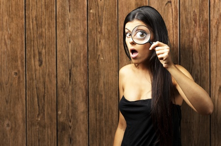 Young woman surprised looking through a magnifying glass against wooden wall Stock Photo - 13280328