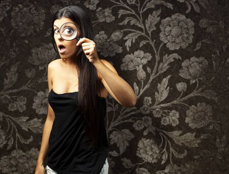 Young woman surprised looking through a magnifying glass against a vintage wall photo