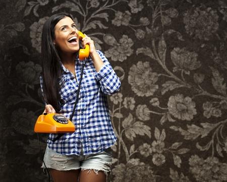 portrait of young woman talking on vintage telephone against a vintage wall photo