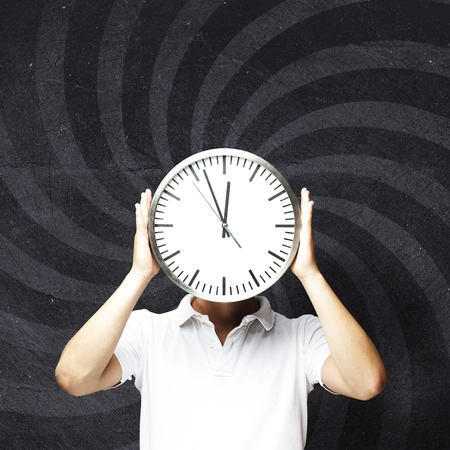 young man hiding his face behind a clock against an abstract background photo