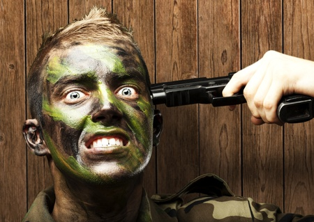 portrait of young soldier comiting suicide against a wooden wall photo