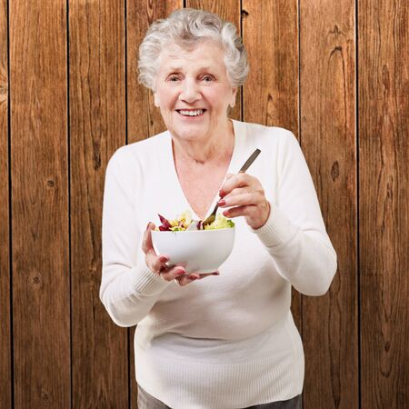 portrait of senior woman eating salad against a wooden wall photo