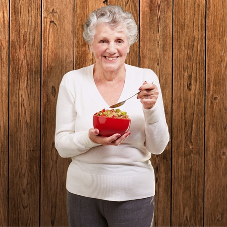 old people eating: portrait of senior woman holding a cereals bowl against a wooden wall Stock Photo