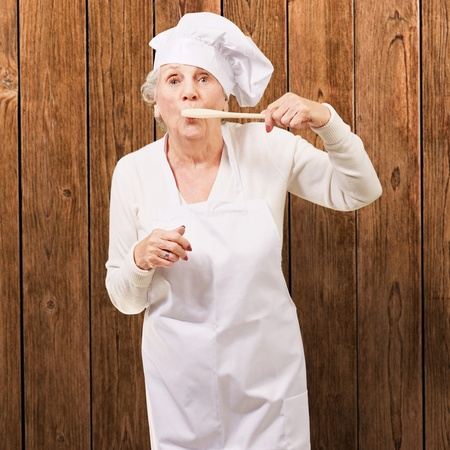 granny: portrait of cook senior woman with wooden spoon on mouth against a wooden wall Stock Photo